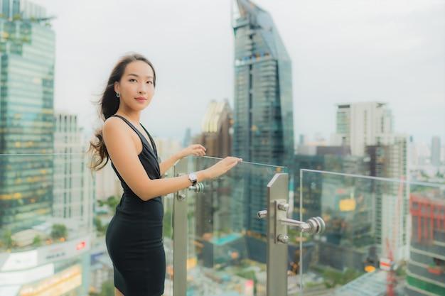 肖像画の美しい若いアジア女性はリラックスして屋上にレストランをお楽しみください 無料写真