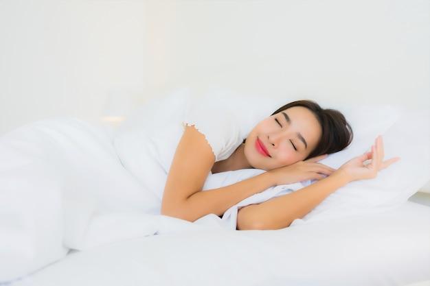 La bella giovane donna asiatica del ritratto si rilassa il sorriso felice sul letto con la coperta di cuscino bianca Foto Gratuite