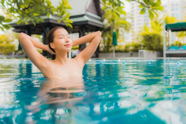 Portrait beautiful young asian woman relax happy smile leisure around outdoor swimming pool Free Photo