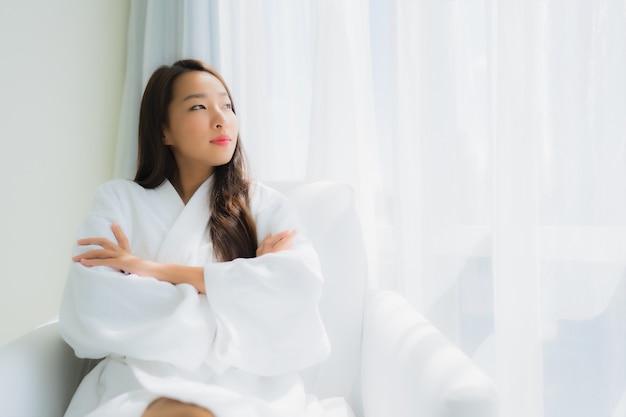 肖像画の美しい若いアジア女性はソファの上のコーヒーカップで幸せな笑顔をリラックスします。 無料写真
