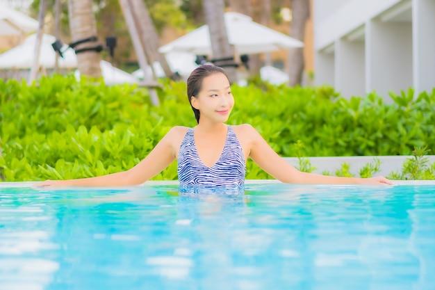 肖像画美しい若いアジアの女性は海の海のビーチと屋外スイミングプールの周りのレジャーをリラックス 無料写真