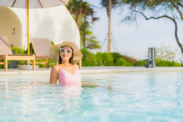 肖像画美しい若いアジアの女性は海と屋外スイミングプールの周りのレジャーをリラックス 無料写真