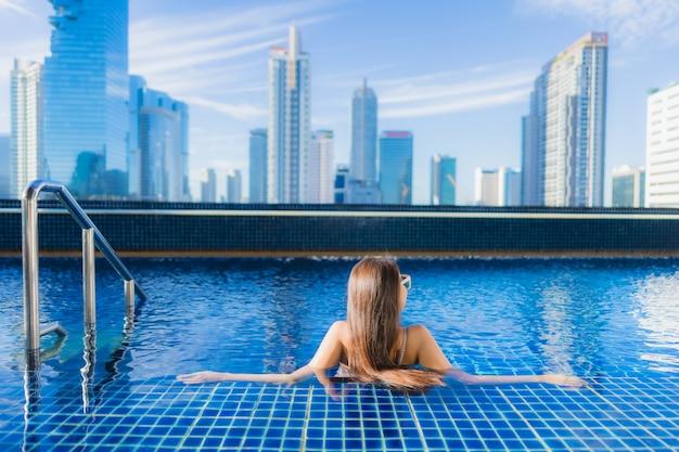 Женщина портрета красивая молодая азиатская ослабляет отдых наслаждается вокруг открытого бассейна Бесплатные Фотографии