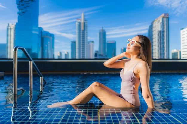 肖像画の美しい若いアジア女性リラックスレジャー屋外スイミングプールの周りを楽しむ 無料写真