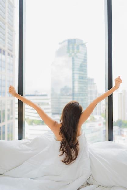 Женщина портрета красивая молодая азиатская ослабляет отдых на кровати с видом на город Бесплатные Фотографии