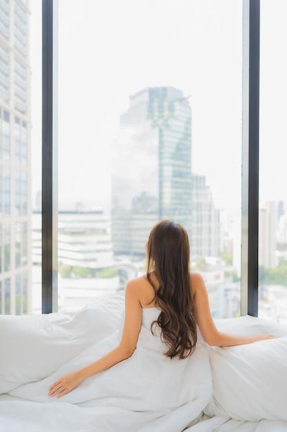 肖像画美しい若いアジア女性はシティービューのベッドでレジャーをリラックスします。 無料写真