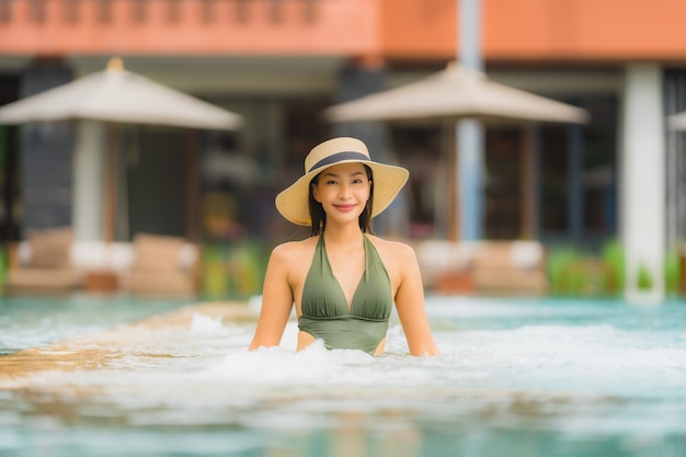 Portrait beautiful young asian woman relax in luxury outdoor swimming pool in hotel resort nearly beach sea ocean Free Photo
