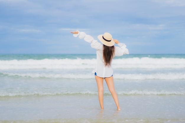 La bella giovane donna asiatica del ritratto si rilassa il sorriso intorno all'oceano del mare della spiaggia nel viaggio di viaggio di vacanza di festa Foto Gratuite
