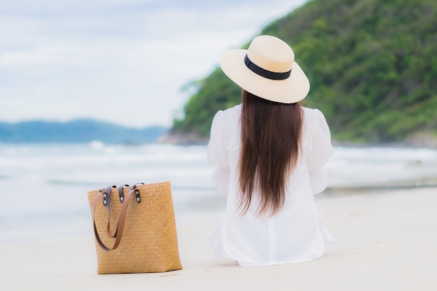 Женщина портрета красивая молодая азиатская ослабляет улыбку вокруг океана моря пляжа в поездке каникул праздника Бесплатные Фотографии