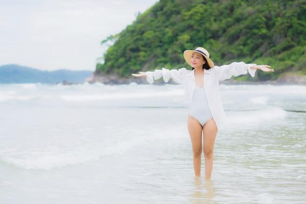 肖像画美しい若いアジアの女性は、休日の休暇旅行旅行でビーチの海の海の周りの笑顔をリラックス 無料写真
