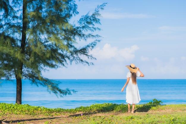 초상화 아름 다운 젊은 아시아 여자 여행 휴가를위한 푸른 하늘 흰 구름과 해변 바다 바다 주위에 미소를 휴식 무료 사진