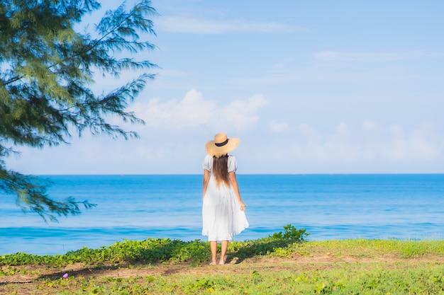 La bella giovane donna asiatica del ritratto si rilassa il sorriso intorno all'oceano del mare della spiaggia con la nuvola bianca del cielo blu per le vacanze di viaggio Foto Gratuite