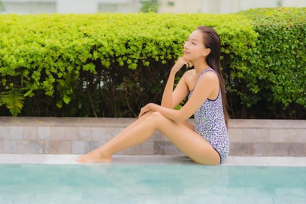 肖像画の美しい若いアジアの女性は、レジャーや休暇のための屋外スイミングプールの周りの笑顔をリラックスします。 無料写真