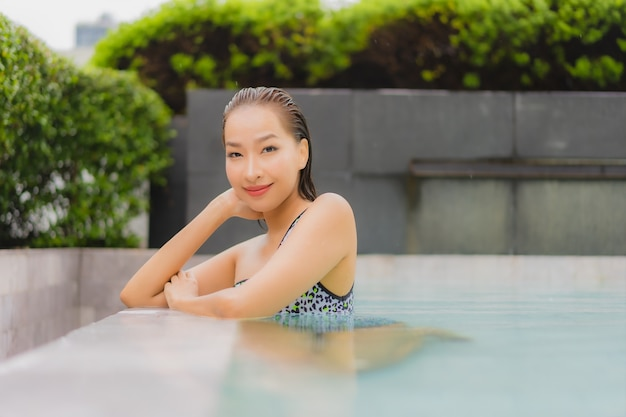 Женщина портрета красивая молодая азиатская ослабляет улыбку вокруг открытого бассейна для отдыха и каникул Бесплатные Фотографии