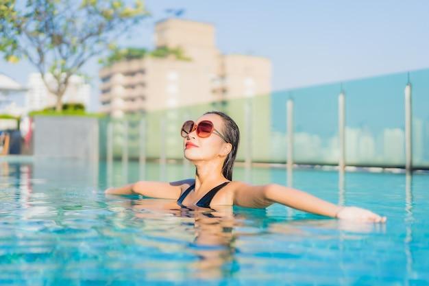 초상화 아름 다운 젊은 아시아 여자는 호텔 리조트에서 야외 수영장 주위에 미소를 긴장 무료 사진