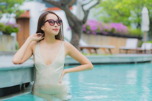 肖像画の美しい若いアジア女性は屋外スイミングプールの周りの笑顔をリラックスします。 無料写真