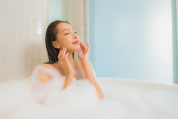 Portrait beautiful young asian woman relax smile in bathtub at bathroom interior Free Photo