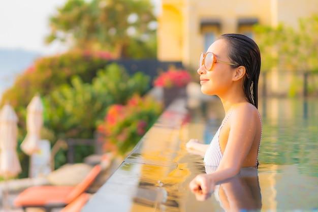 肖像画美しい若いアジアの女性は笑顔をリラックスして休暇でリゾートホテルのプールの周りのレジャーをお楽しみください 無料写真