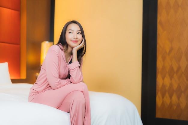 Женщина портрета красивая молодая азиатская ослабляет улыбку счастливую на кровати в интерьере спальни Бесплатные Фотографии