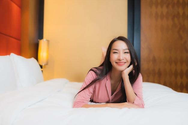 肖像画の美しい若いアジア女性は寝室のインテリアのベッドで幸せな笑顔をリラックス 無料写真