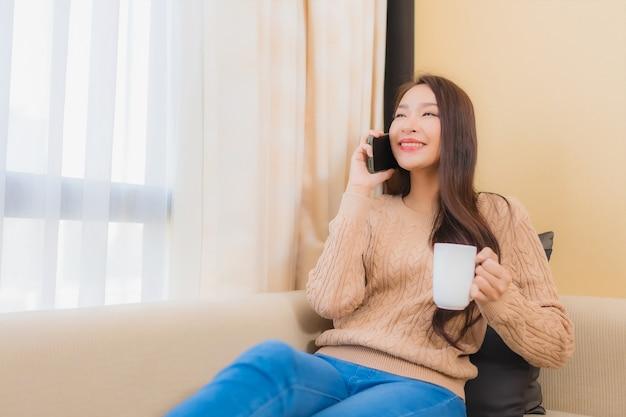 肖像画の美しい若いアジアの女性はソファーでコーヒーを飲みながらスマートフォンに満足して笑顔をリラックスします。 無料写真