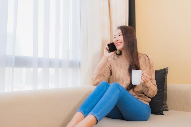 La bella giovane donna asiatica del ritratto si rilassa il sorriso felice con lo smart phone con il caffè sul sofà Foto Gratuite