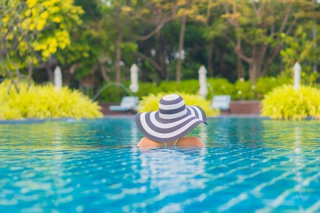 초상화 아름 다운 젊은 아시아 여자는 거의 바다에 가까운 야외 수영장 주변 미소 레저 휴식 무료 사진