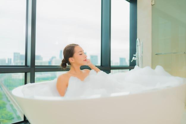 肖像画の美しい若いアジア女性はバスルームのインテリアでバスタブで笑顔レジャーをリラックスします。 無料写真
