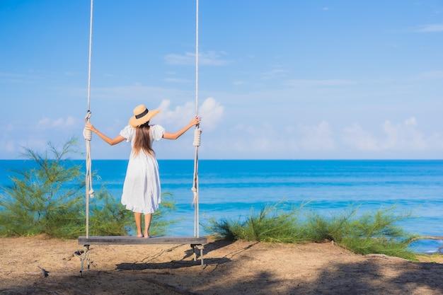 La bella giovane donna asiatica del ritratto si rilassa il sorriso sull'oscillazione intorno all'oceano del mare della spiaggia per il viaggio della natura in vacanza Foto Gratuite