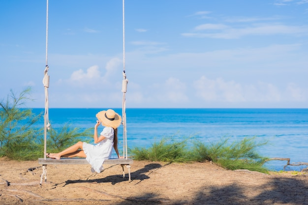 Portrait beautiful young asian woman relax smile on swing around beach sea ocean for nature travel in vacation Free Photo