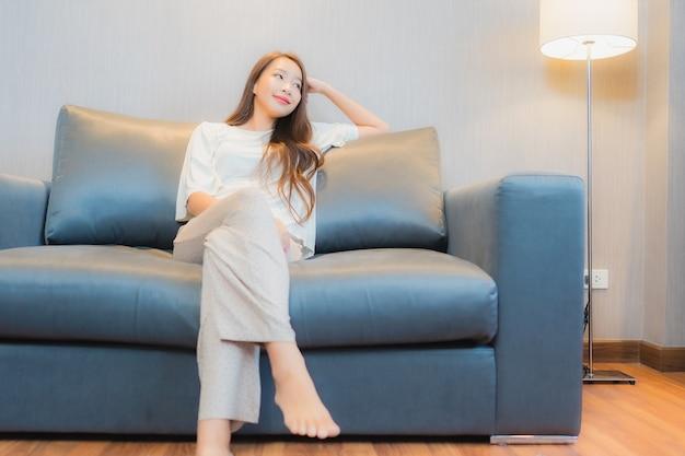 La bella giovane donna asiatica del ritratto si rilassa sul sofà nell'interno del salone Foto Gratuite