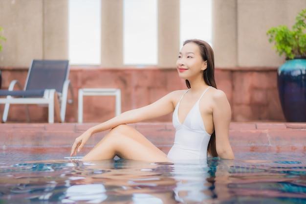 Ritratto di bella giovane donna asiatica si rilassa in piscina Foto Gratuite