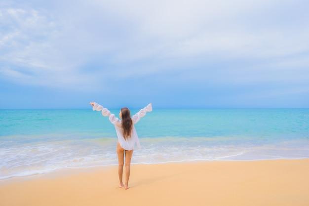 Ritratto di bella giovane donna asiatica che si rilassa intorno all'oceano del mare della spiaggia nella vacanza di viaggio Foto Gratuite