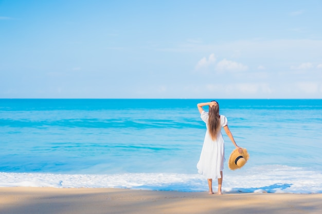 Ritratto di bella giovane donna asiatica che si rilassa intorno alla spiaggia con le nuvole bianche sul cielo blu in vacanza di viaggio Foto Gratuite