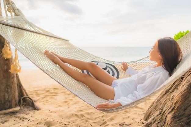 Ritratto di bella giovane donna asiatica che si rilassa sull'amaca intorno alla spiaggia in vacanza Foto Gratuite