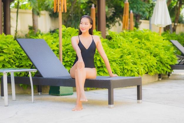 Ritratto di bella giovane donna asiatica che si rilassa intorno alla piscina all'aperto nella località di soggiorno dell'hotel Foto Gratuite