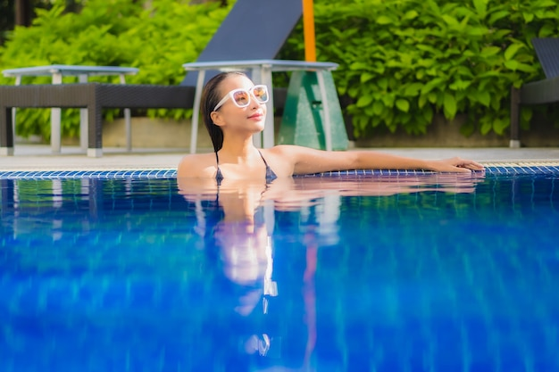 Portrait of beautiful young asian woman relaxinging around outdoor swimming pool in hotel resort Free Photo