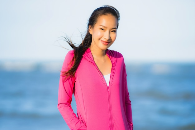 Portrait beautiful young asian woman running or exercise on the tropica nature landscape of beach Free Photo