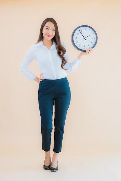 肖像画の美しい若いアジア女性は目覚まし時計を表示します。 無料写真