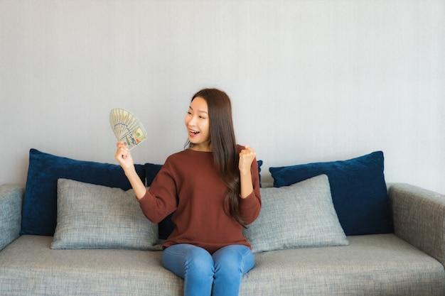 肖像画の美しい若いアジアの女性は、リビングルームのインテリアのソファーに現金とお金を表示します。 無料写真