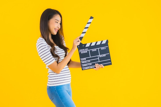 Portrait beautiful young asian woman show clapper movie board Free Photo