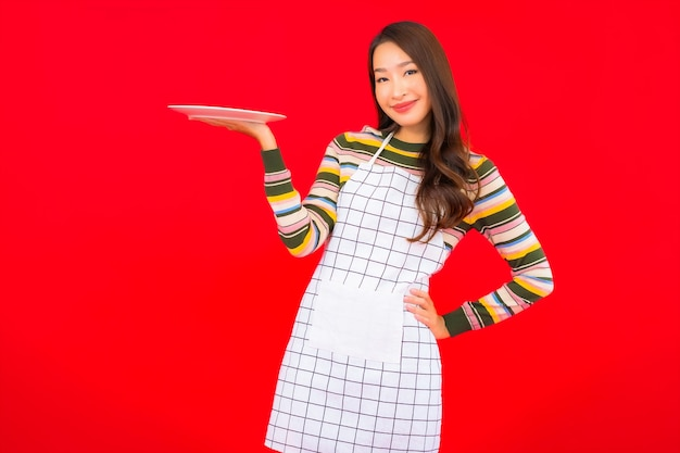 La bella giovane donna asiatica del ritratto mostra il piatto vuoto sulla parete rossa Foto Gratuite