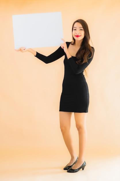 肖像画の美しい若いアジア女性は空のホワイトボードを表示します。 無料写真