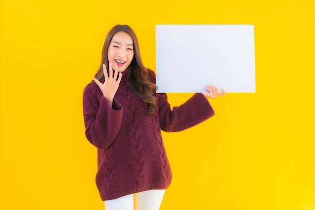 肖像画美しい若いアジアの女性は空の白い板紙を表示します 無料写真