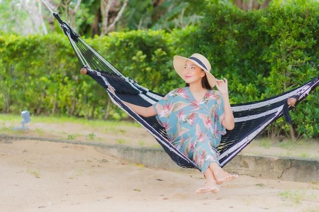 La bella giovane donna asiatica del ritratto si siede sull'oscillazione dell'amaca intorno all'oceano del mare della spiaggia in vacanza di festa Foto Gratuite