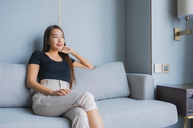 ソファの上に座って美しい若いアジア女性の肖像画はリビングルームエリアでリラックスします。 無料写真