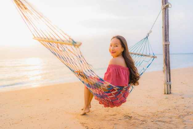 Portrait beautiful young asian woman sitting on the hammock with smile happy neary beach sea and oce Free Photo