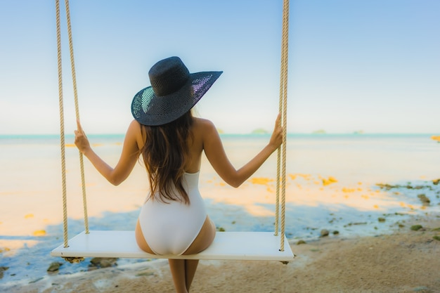 Portrait beautiful young asian woman sitting on the swing around beach sea ocean for relax Free Photo