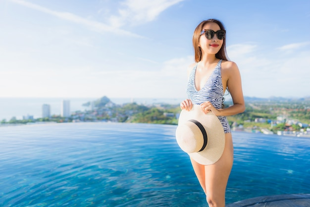 Portrait beautiful young asian woman smile happy relax around swimming pool in hotel resort for leisure Free Photo
