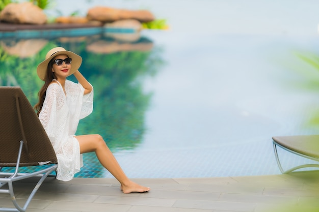 Il bello giovane sorriso asiatico della donna del ritratto felice si rilassa intorno alla piscina nella località di soggiorno dell'hotel Foto Gratuite